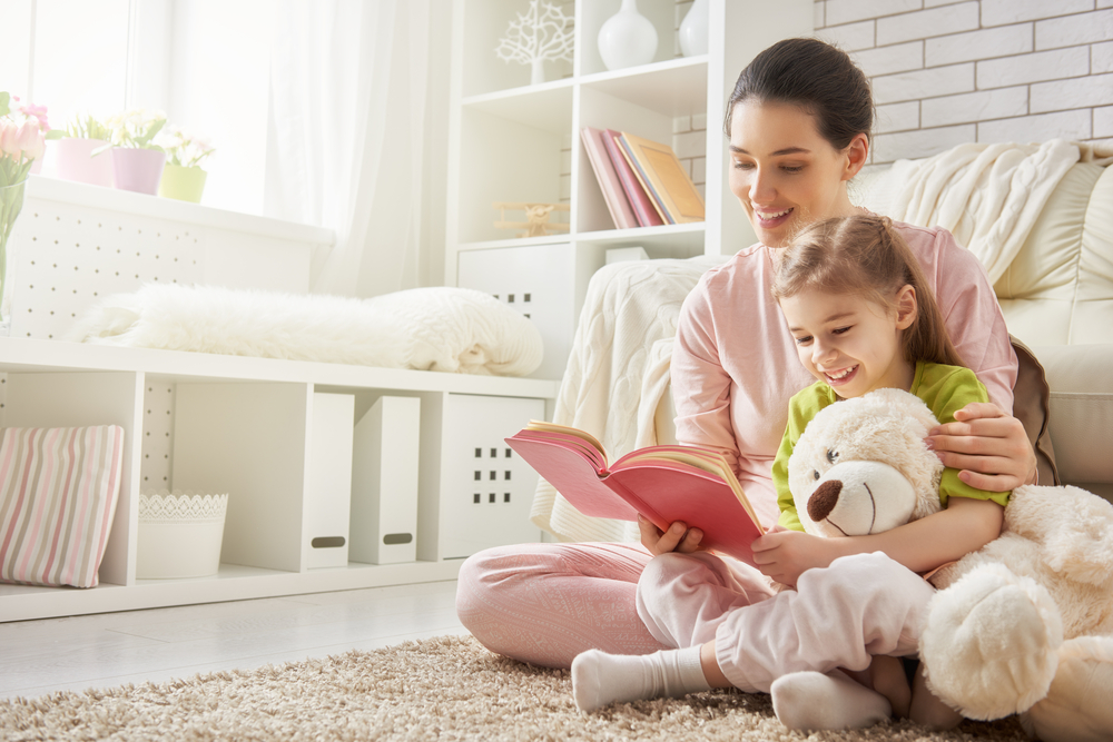 A mom and daughter read a book together on the living room floor